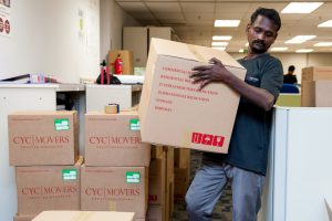 CYC Worker Moving Packed Boxes For Office Relocation