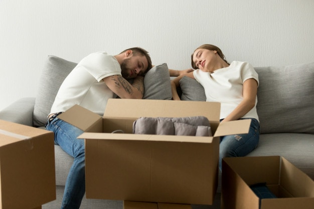 Couples tired from unpacking boxes after home moving