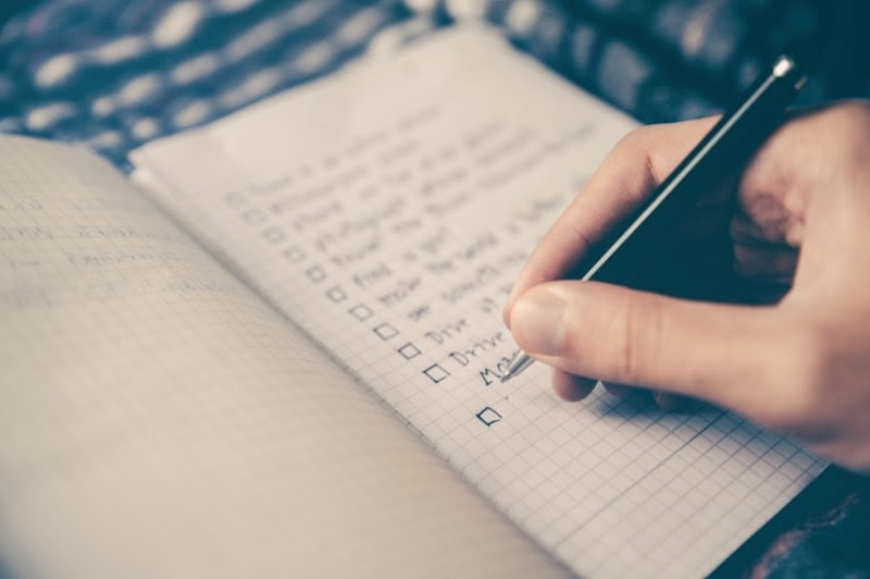 An individual preparing a To-do list before moving in a new house