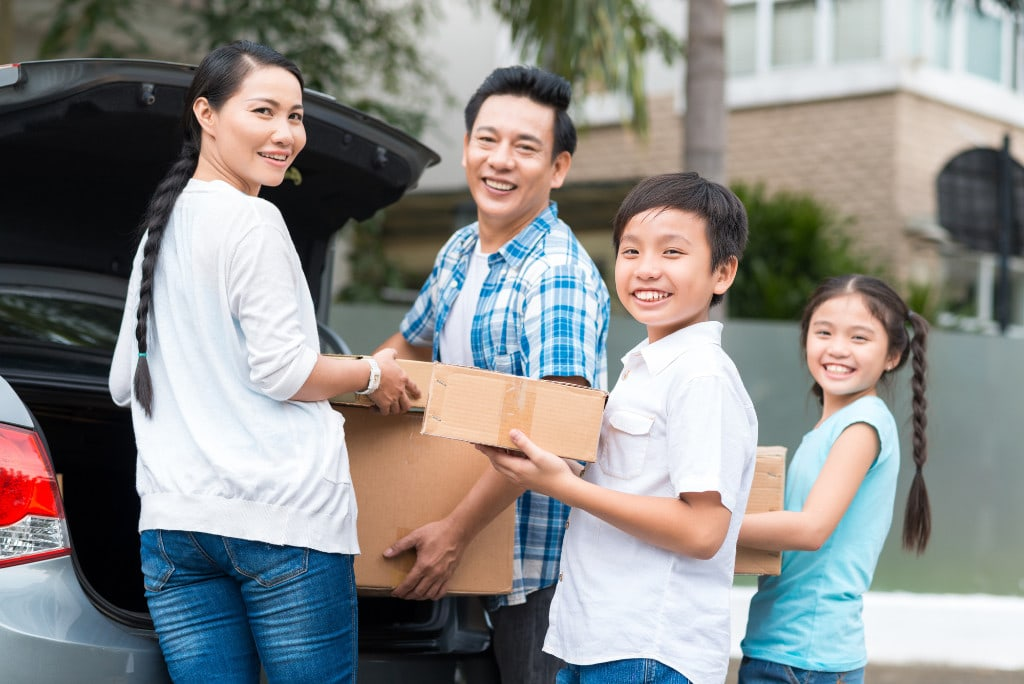 Family with cardboard boxes, moving into a new house